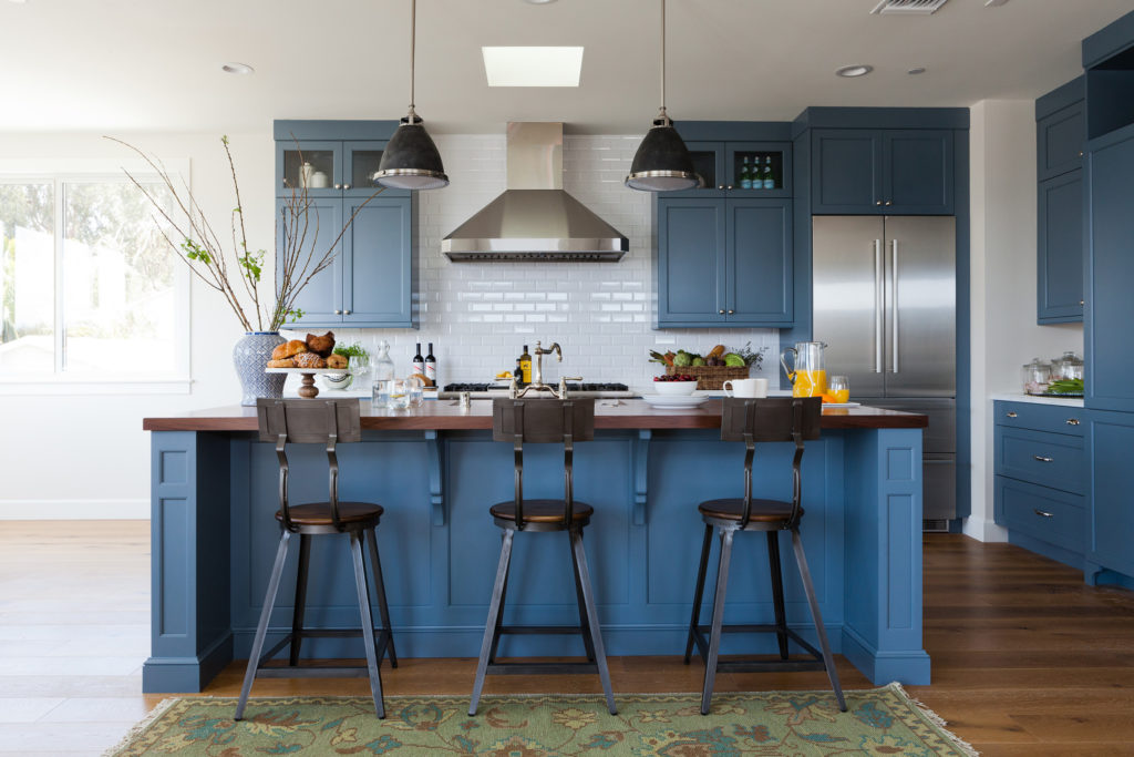 Blue kitchen wood countertop metal barstools white subway tile designed by Kate Lester Interiors