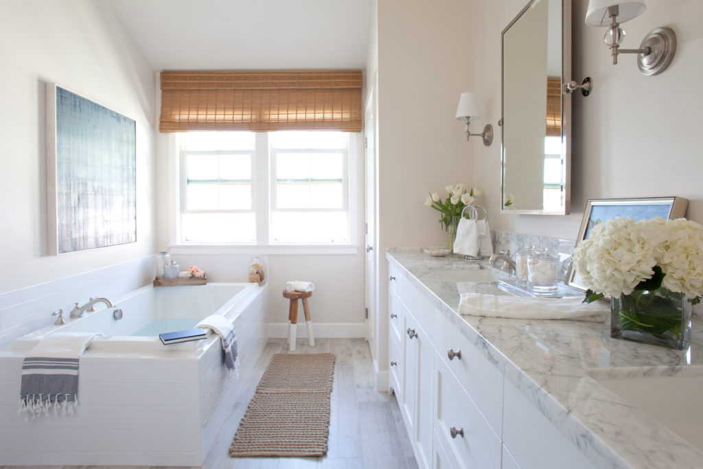 White bathroom with bathtub marble countertop and white cabinets designed by Kate Lester Interiors