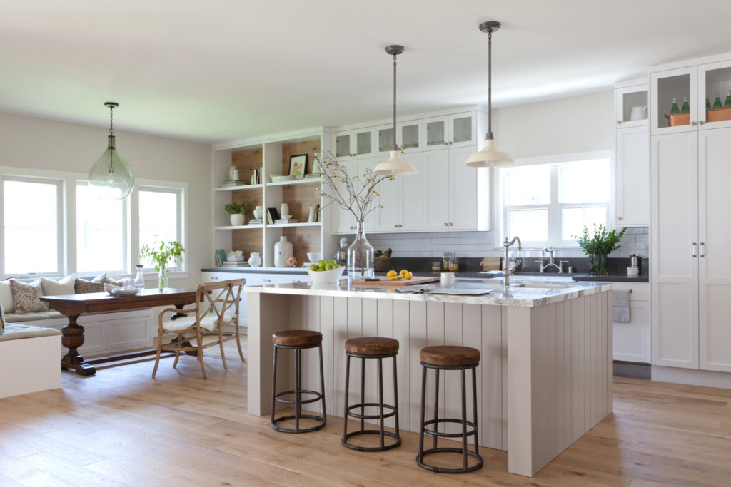 White farmhouse Kitchen with banquette breakfast nook and white countertops wood floors subway tile backsplash and wood barstools designed by Kate Lester Interiors