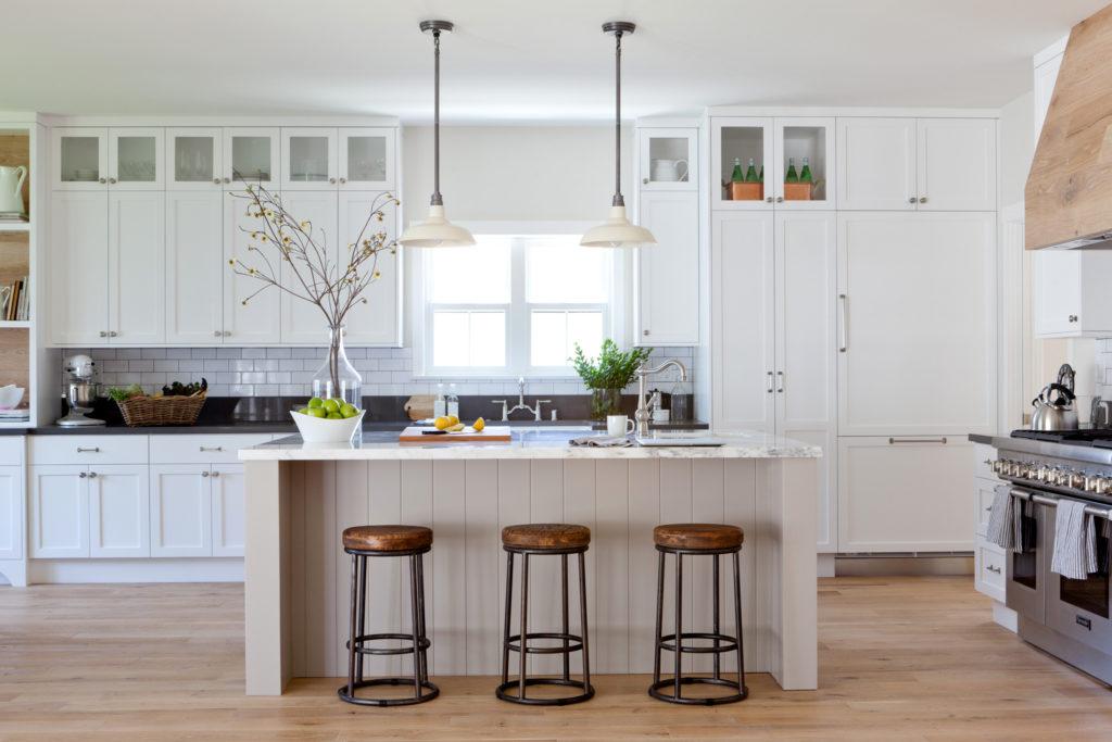White farmhouse Kitchen white countertops wood floors subway tile backsplash and wood barstools designed by Kate Lester Interiors
