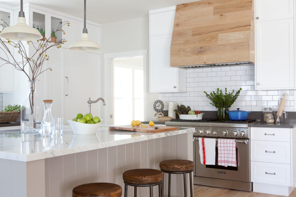 White paint farmhouse kitchen and gray island and wood hood over range.