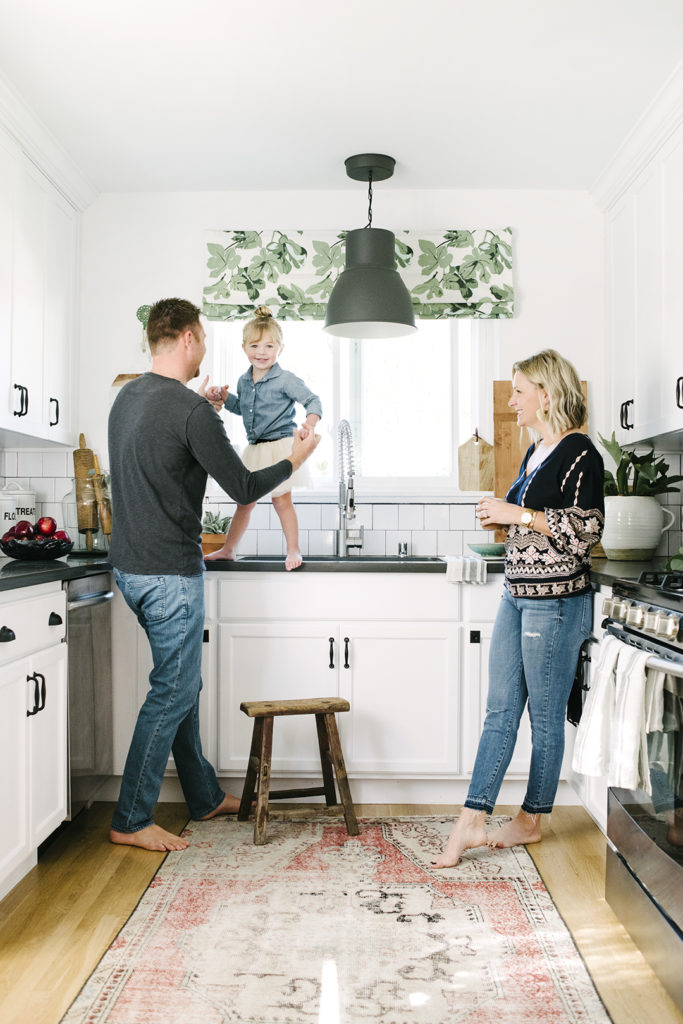 White kitchen black countertops wood floors and vintage rug remodel after image designed by Kate Lester Interiors