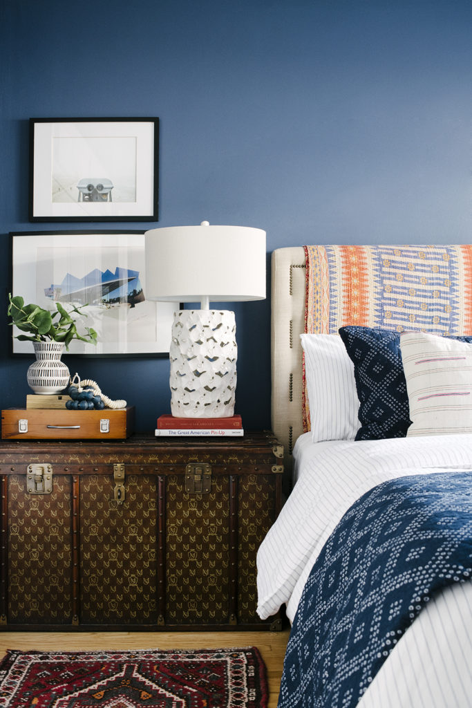 Bedroom with Navy blue walls vintage nightstand and rug and patterned bedding designed by Kate Lester Interiors
